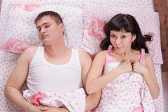 girl with surprise woke a sleeping man in bed - stock photo