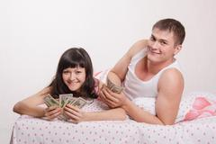Happy girl and guy with wad of money in bed Stock Photos