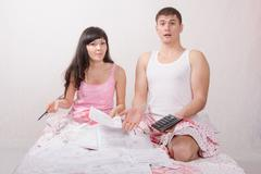 young couple sitting in bed, shocked by amount of accounts - stock photo