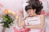 Stock Photo of on bed next to sleeping young girl lay flowers