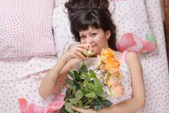 beautiful girl enjoying scent of flowers in bed - stock photo