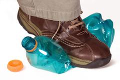Man's foot stepping on a plastic bottle Stock Photos