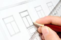 Architect draws a window in the house plan Stock Photos