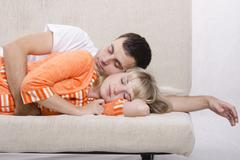 Young couple sleeping on the couch Stock Photos