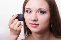 makeup artist brush powder on face causes model - stock photo