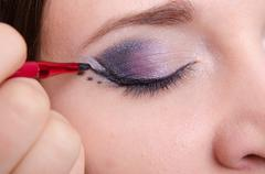 makeup artist draws arrows on the eyelids model - stock photo