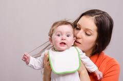 Six-month baby girl in bib tear your hair mom Stock Photos