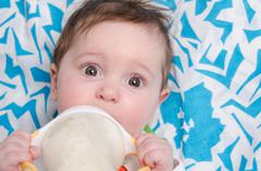 Six-month girl drinking milk formula from a bottle Stock Photos
