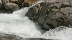 Water flowing and splashing over rocks in a mountain torrent. 4K UHD Stock Footage