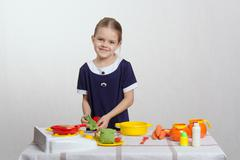 five year old girl puts cabbage leaf in pan - stock photo
