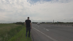 Young man hitch-hiking on highway freeway making by hand so any car stops  Stock Footage