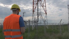 Engineer going to energy power station working on laptop checking gathering info - stock footage