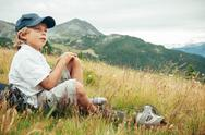 Stock Photo of young boy takes a rest in a meadow during a mountain trek.