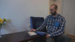 Young man working in remote system using laptop sitting relaxed on blue armchair Stock Footage