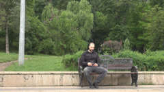 Young man sitting on bench pulling out of pocket mobile phone and enjoy gaming Stock Footage