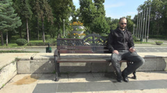 Man in sunny day staying alone on a bench in park listening music on smart phone Stock Footage