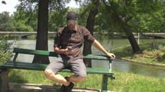 Man has relax time in the park lake background view while talking on smart phone Stock Footage