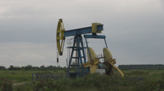 Oil pump extracting fossil fuel energy oil drilling in grass field cloud on sky  Stock Footage