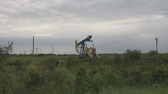 Isolated pump-jack unit drilling oil petrol nature with heavy sky in background Stock Footage