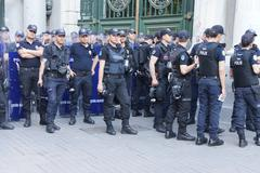 Police in riot gear await orders during a protest Stock Photos