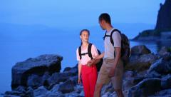 Two backpackers walk on rocky coast of big lake Stock Footage