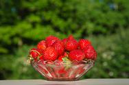 Stock Photo of bowl with fresh strawberries at green background