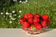 Stock Photo of fresh strawberries on a table  in garden