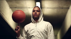 Portrait of a hooded street ball basketball player spinning a ball at night Stock Footage
