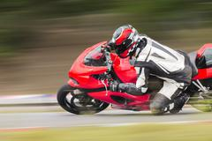 Motorcycle practice leaning into a fast corner on track Stock Photos