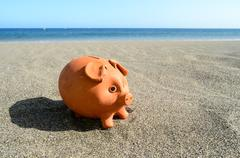 Stock Photo of coin bank on sand