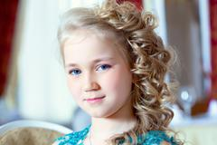 Portrait of little blue-eyed girl with ringlets - stock photo