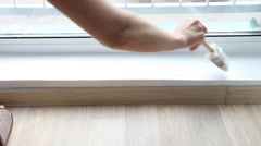 Female hand holding a brush and painting windowsill - stock footage