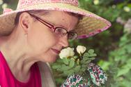 Mature woman and white rose Stock Photos