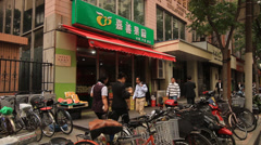People walking in front of a vegetable shop in Shanghai Stock Footage