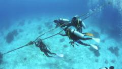 Scuba divers hanging onto anchor rope to perform safety stop at end of dive Stock Footage