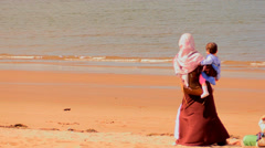 Arab woman with a child on the beach. Veil in the wind Stock Footage