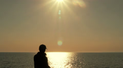 Man stands at the pier and lights cigarette Stock Footage