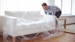 Male putting down new sofa at home Stock Footage
