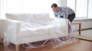 Stock Video Footage of male putting down new sofa at home
