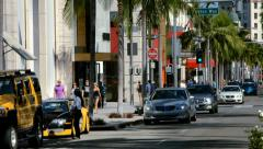 Luxury cars drive on Rodeo Drive in Beverly Hills in Los Angeles, California 4K Stock Footage