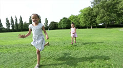 Two young girls running in a wide open grass space Stock Footage