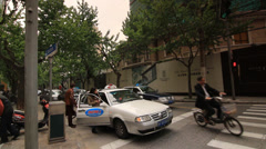 Passenger boarding a Taxi in Shanghai in front of real estate ad Stock Footage
