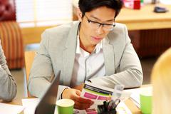 Asian businessman in glasses sitting at the table and reading instruction in  Stock Photos