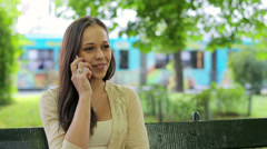 Young woman talking on cellphone in the city park HD - stock footage