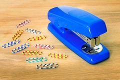 Stapler of bright blue color and paper clip against a table. Stock Photos