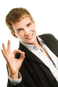 Handsome young man showing ok gesture. isolated on white background Stock Photos