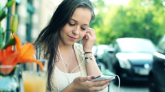 Attractive young woman listening music on smartphone in cafe HD Stock Footage