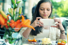 Woman taking photo of tasty dessert with cellphone in cafe NTSC - stock footage