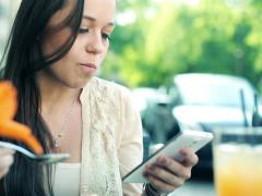 Young woman texting on smartphone and eating dessert in cafe NTSC Stock Footage