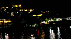 Hotels in mountains at night with lights on background of ripples In sea. Video Stock Footage